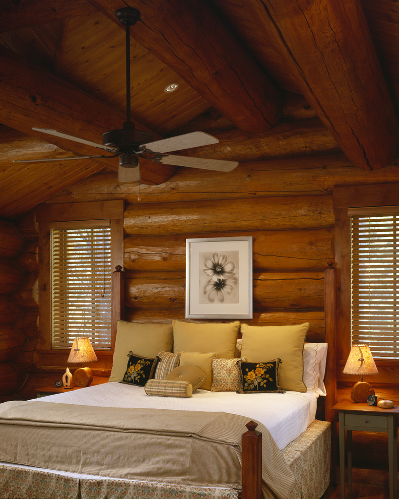 logs bedroom interior for cabin logs wall systems wooden bed without headboard small wood bedside tables two table lamps white linen coat beige blanket ceiling fan windows with shutter some wall arts