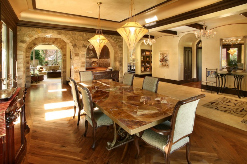 mediterranean dining room with wooden flooring, earthy color wall and ceiling, stones arch wall, marble top table in brown and wooden chair in beige