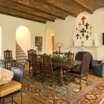 mediterranean dining room with wooden flooring, stones ceiling, white walls, wooden table set, crosses on the wall