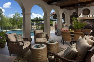 mediterranean summer kitchen with brown tiles, earthy color palette of brown, wooden chairs, wooden couches, arch walls