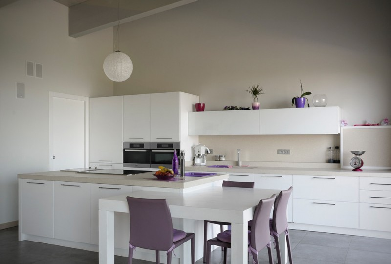 minimalist eat in kitchen with flat paneled cabinetry light beige backsplash grey ceramic floors white kitchen island integrated with table bar modern purple stools stainless steel appliances