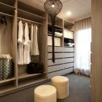Minimalist Wooden Walk In Closet System Furnished With A Couple Of Light Beige Chairs Wooden Floors Glass Window With Thin Linen Curtain And Decorative Pendant Lamp