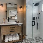 Modern Bathroom With Little Rustic Accents Wooden Vanity Cabinet White Top Vanity Black White Tiles Floors With Traditional Patterns Light Grey Subway Tiles For Shower Walls Black Finished Fixtures