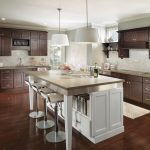 Modern Kitchen With White Island, Dark Wood Cabinet, Wooden Floor, Light Backsplash,white Pendant