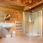 Modern Rustic Bathroom With Corner Walk In Shower Space Glass Shower Partition Beige Ceramic Floors And Walls Wall Mount Sink Wall Mount Toilet Wooden Walls Mirror With Wood Frames