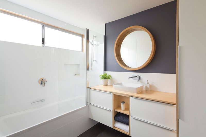 modern small bathroom with grey flooring, white ceramic walls, bathtub and shower, white brown wooden cabinet under brown countertop with white sink, round brown wooden framed mirror on grey wal