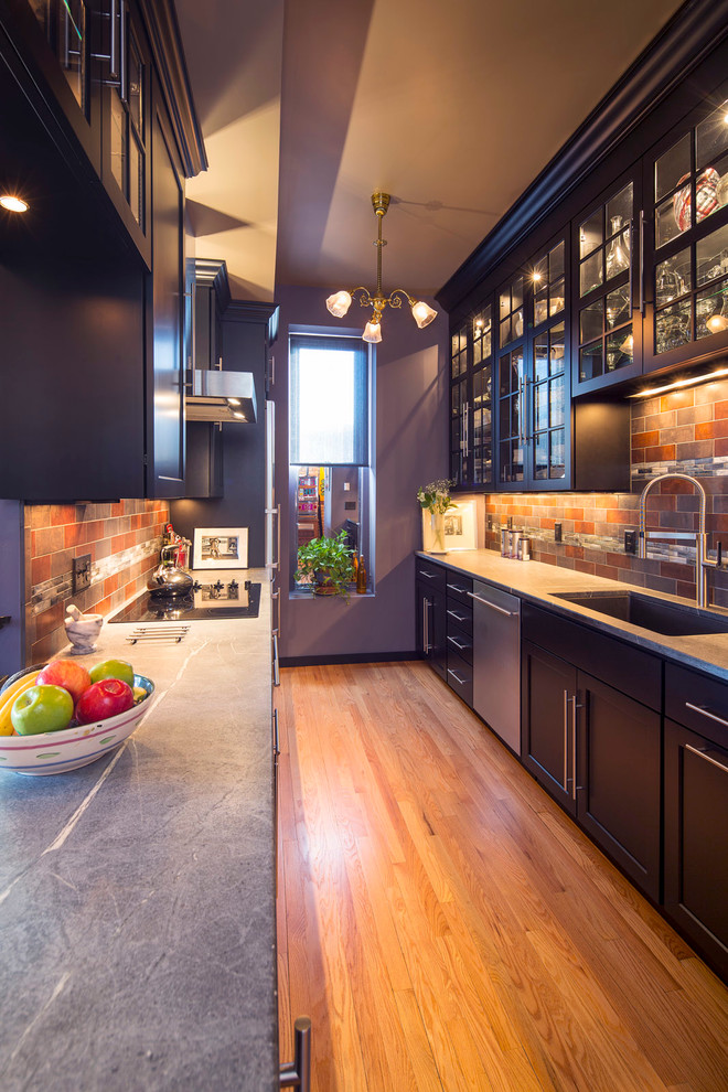 narrow transitional kitchen design dark purple cabinets dark purple shaker cabinets stainless steel appliances red bricks backsplash medium toned wood floors grey countertop