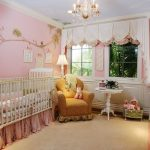 Peach Half Window Curtain With Decortaive Base White Baby Crib With Sweet Pink Linen Yellow Nurturing Chair Pink Wall With Floral Decoration Classic Pendant Lamp Rounded Mirror With White Gold Frame