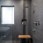 Pebble Tiles And Small Rock Tiles In Black Recessed Shelf Wooden Shower Bench Glass Panel And Door For Shower Space