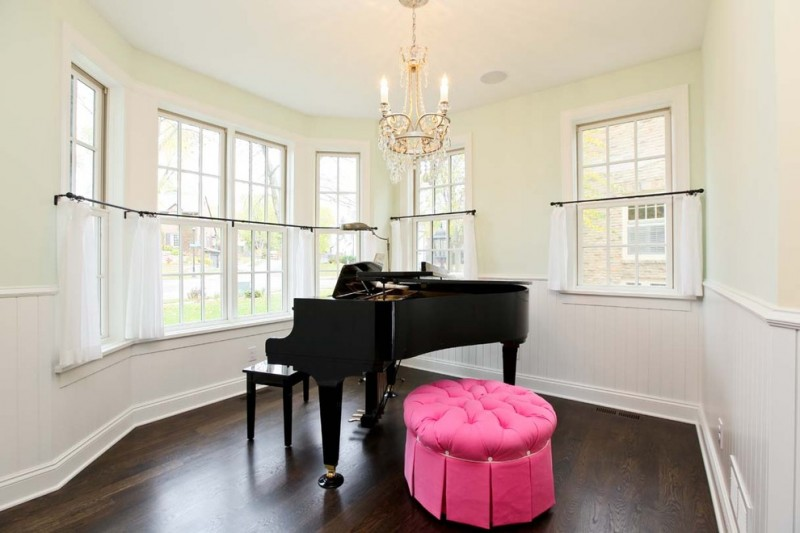 piano room with light yellow wall system white cafe curtains with black wrought iron rods a grand piano sweet pink ottoman chair dark wood floors classic candle pendant lamp