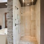 rain head shower beige wall stone tiled wall dark colored ceiling walk in shower space marble floor