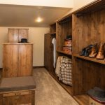 Raw Rustic Walk In Closet Idea With Taller Island And Chair At Center