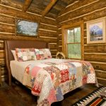 Rustic Bedroom Design Multicolor Duvet Wooden Bed With Leather Headboard Unfinishe Timber Walls Dark Wood Floors Multicolor Rug Glass Windows Old And Tradisional Bedside Tables With Table Lamps