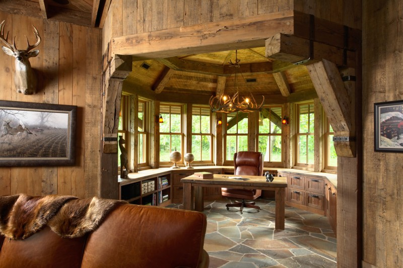 rustic home office surrounded by windows, with blue and brown stone floring, rustic chadelier, wooden table, brown leather chairs