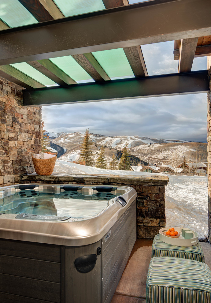 rustic hot tub with stone wall high in one side and half wall in front, glass ceiling