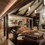 rustic living room open to kitchen with white vaulted ceiling with wooden beams, brown furniture, long barrel vaulted ceiling on the aisle