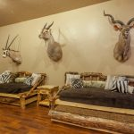 rustic living room with wooden flooring, wood frame couch, animal patter pillows and cushions, wooden hang rack, deer head wall mount