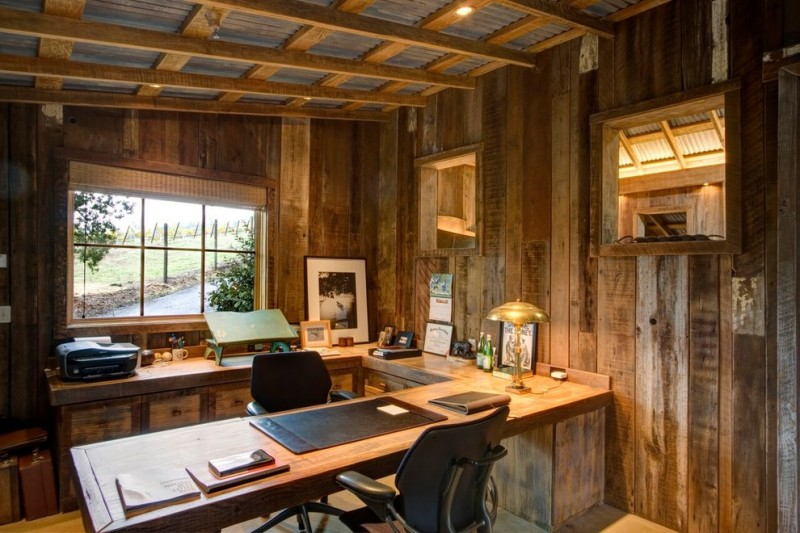 rustic office near the window with asbestos ceiling, wooden wall, wooden L table, adn black leather office chair
