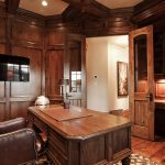 Rustic Office With Wooden Wall, Table, And Floor, And Brown Leater Swivel Chair And Brown Fabric Couch