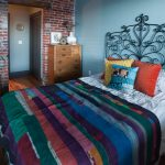 Shabby And Eclectic Bedroom Colorful Bed Quilt Black Wrought Iron Bed With Headboard Red Bricks Walls Wooden Drawer System