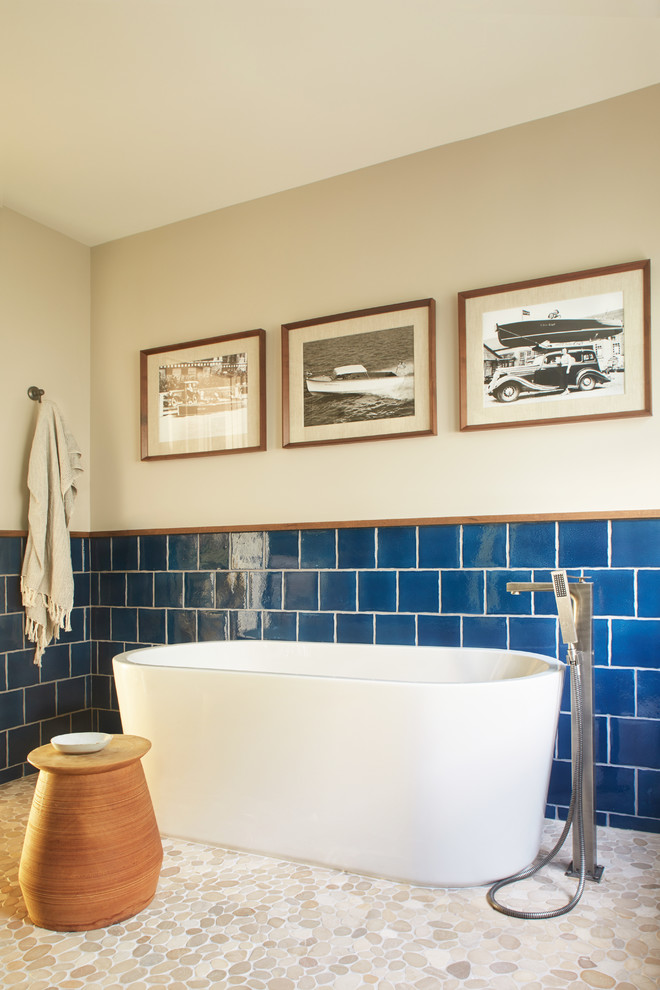 simple bathroom idea with navy blue tiles walls pebble tiles floors white bathtub burnt clay table some hand paintings on walls
