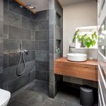 small bathroom with grey floring, grey shower wall, grey wall partition, woodne sink vanities, white bowl sink, white cream wall, white toilet