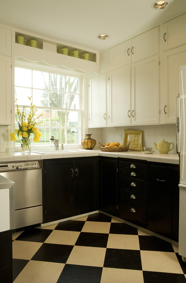 small kitchen with black and white flooring, white wall, countertop, window pane, black cabinet