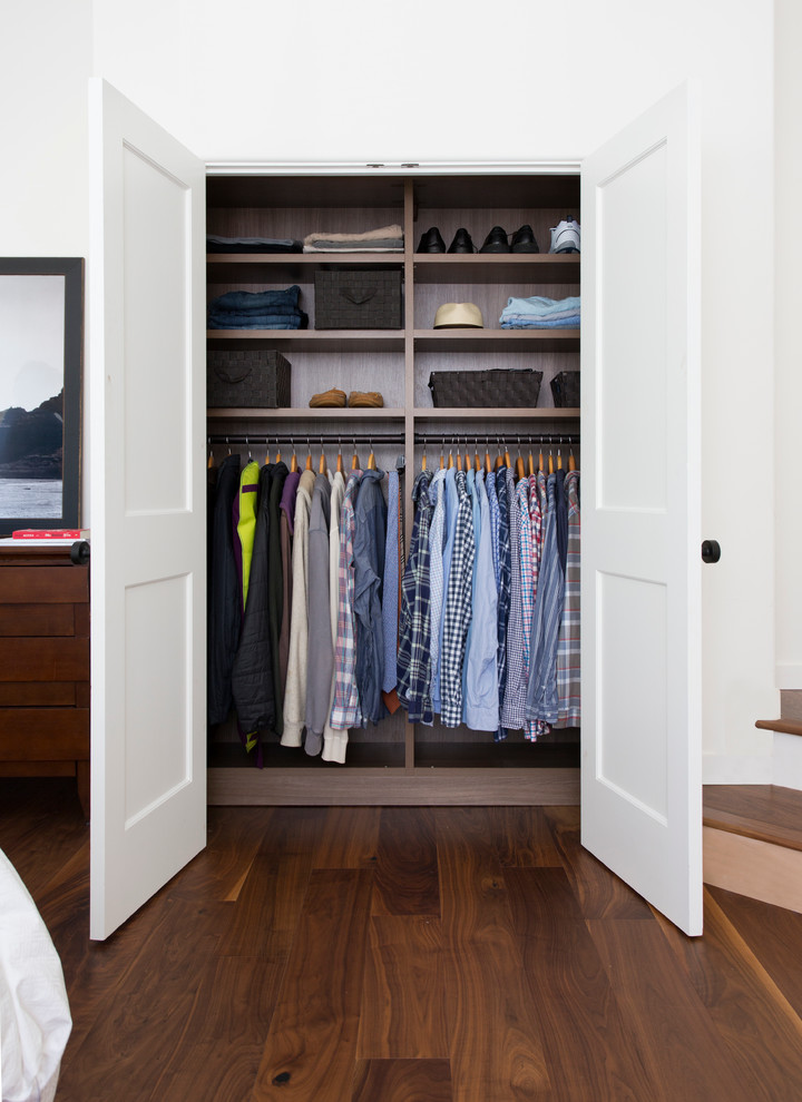 small reach in closet with door panels dark toned wooden floors