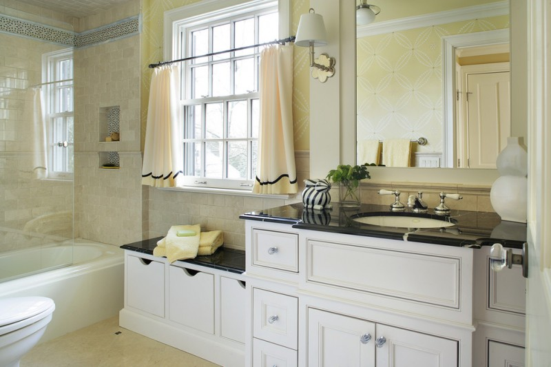 soft yellow cafe curtains with decorative black lines light yellow walls with white accents black countertop white cabinet system white bathtub with half glass panel light yellow tiles