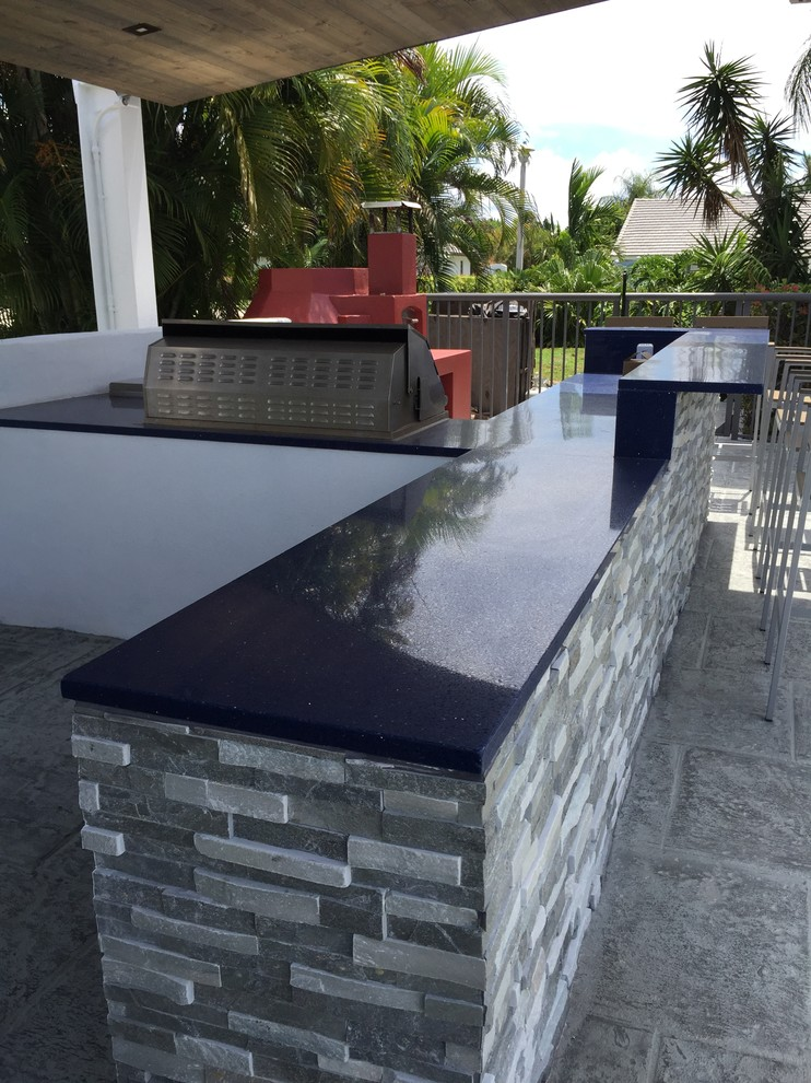 summer kitchen with grey stones counter with black polished marble top and barbeque grill