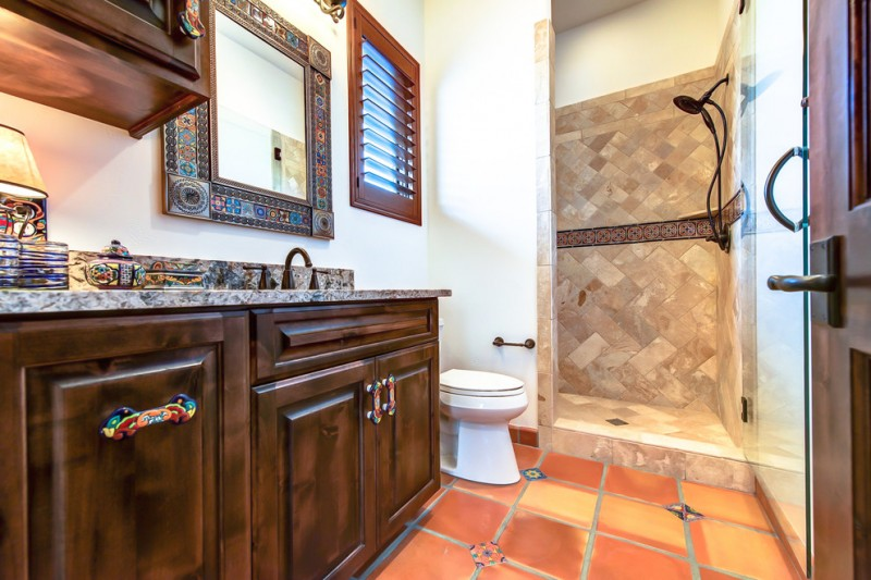 topcoat of granite vanity and dark wood cabinets mirror with art frames yellow orange tiles floors terracotta floors and walls in shower space white toilet