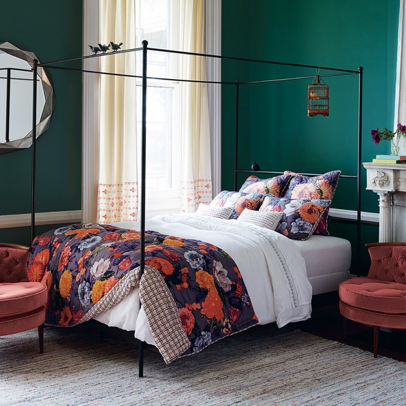 traditional bed room design with black wrought iron bed bloomed flower motif bed quilt and shams chic area rug red chair green walls