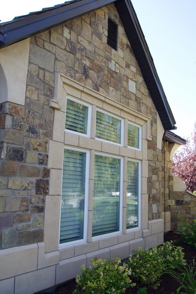 traditional exterior house with natural stones finishing and glass windows with window shutters