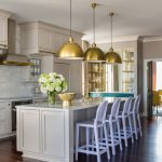 Traditional Kitchen Idea With White Kitchen Island Soft Purple Stools Dark Wood Floors Gold Toned Pendant Lamps Light Beige Cabinets White Stone Backsplash