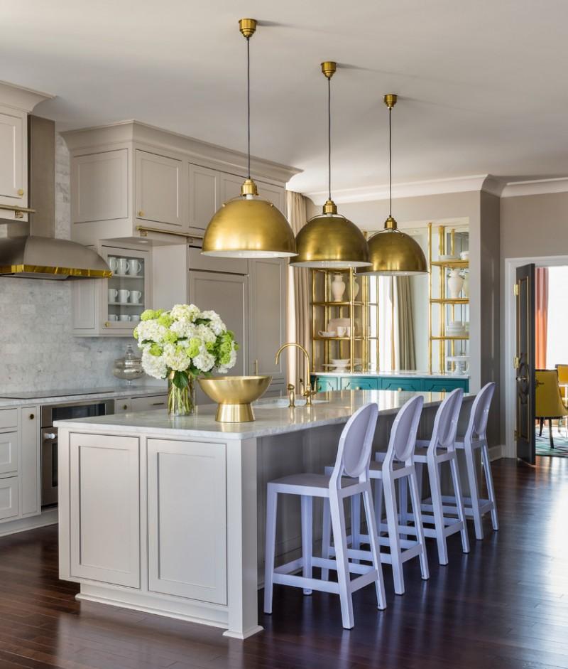 traditional kitchen idea with white kitchen island soft purple stools dark wood floors gold toned pendant lamps light beige cabinets white stone backsplash