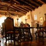 traditional mediterranean dining room with lots of wood beam ont he ceiling, wooden flooring, wooden table set, white wall
