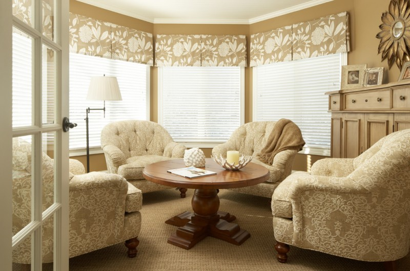 traditional sunroom design with soft beige valance style window curtains white window shades cozy sofas rounded center table soft beige rug