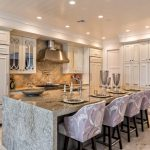 Transitional Eat In Kitchen With Warm Purple Stools Glossy Grey Kitchen Island Integrated With Table Bar Beige Diamond Shaped Tiles For Backsplash Recessed White Cabinetry Stainless Steel Appliances