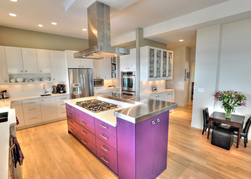 trendy L shaped kitchen idea with deep toned lavender kitchen island with extra storage white flat panel cabinetry stainless steel appliances white backsplash wood floors