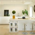 Trendy Kitchen Design In Dominant White Color White Flat Panel Cabinetry White Kitchen Island With Under Shelves Modern Bar Stools Undermount Sink Built In Storage