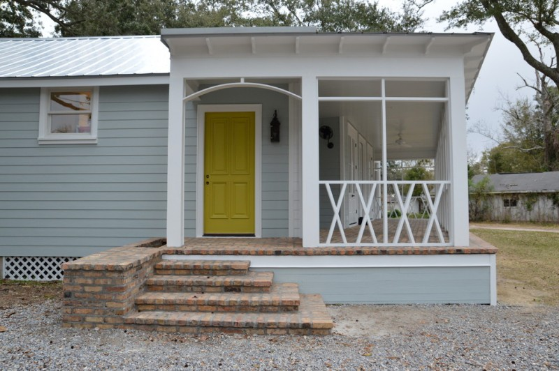 trendy porch supported with red brick pavers light grey siding bright yellow front door and x shape front railing system