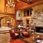 Two Floor Stone And Log House Living Room Fireplace Carpet Wood Floor Chairs Shelves Painting Cabinets Table Lighting Books Glass