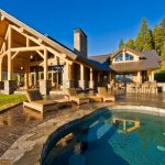 two floor stone and log house pool outdoor dining area chairs table stone and log pillars doors windows roof stones logs