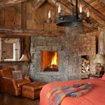 Two Floor Stone And Log House Sofa Bed Pillow Stone Wall Logs Fireplace Chandelier Bedroom Rustic Look
