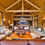 Two Floor Stone And Log House Sofa Fireplace Logs Doors Stone Floor Pillows Table Lighting Windows Glass