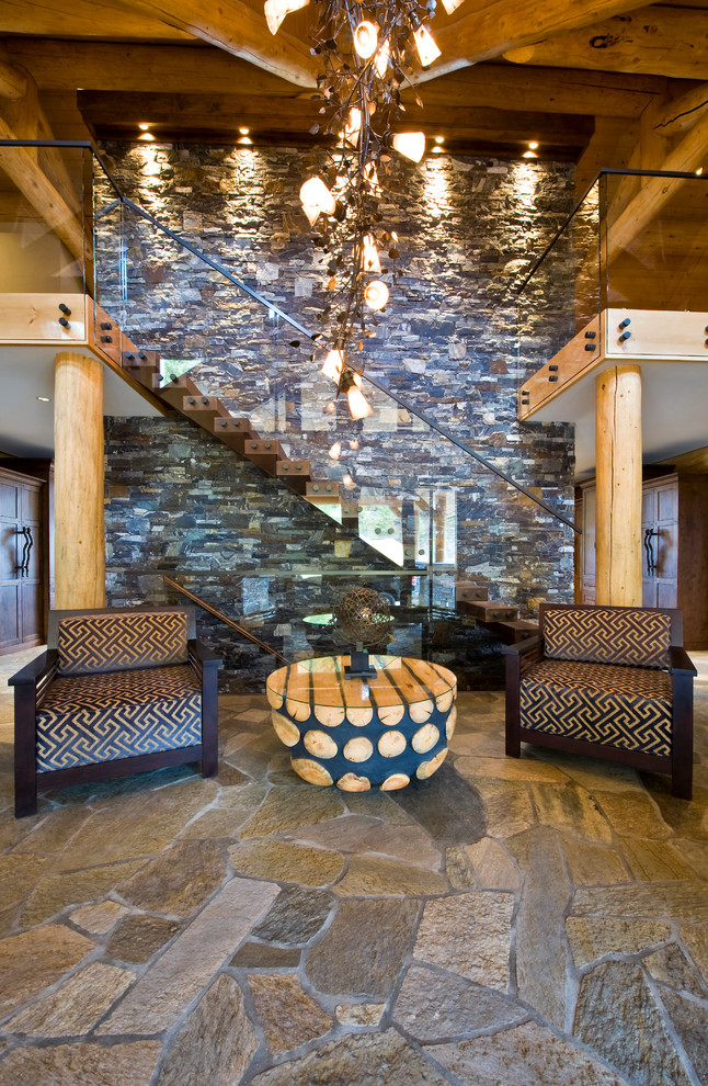 two floor stone and log house stone floor seating stairs glass log pillars ceiling lighting table storage items