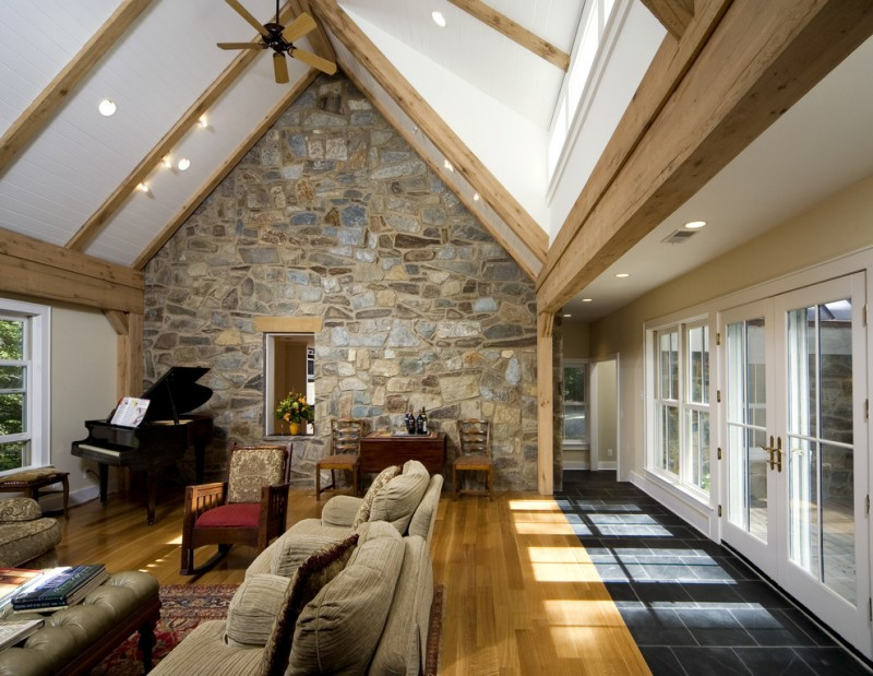 vaulted living room with white ceiling and walls, stone wall in one side, wooden flooring, brown sofa and chair, brown ceiling fan