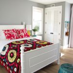 White Bed Sheet With Colorful Blanket And Pillows White Headboard White Bedside Table Pull Up Window In White Turquoise Decorative Chair White Recessed Closet System Wooden Floors Without Finish