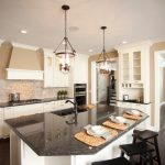 white cabinet black granite countertop cream wall glass ceiling lights brick wall dark hardwood floor