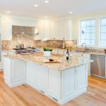 white cabinet granite countertop beige tiled backsplash light hardwood floor stainless steel appliances